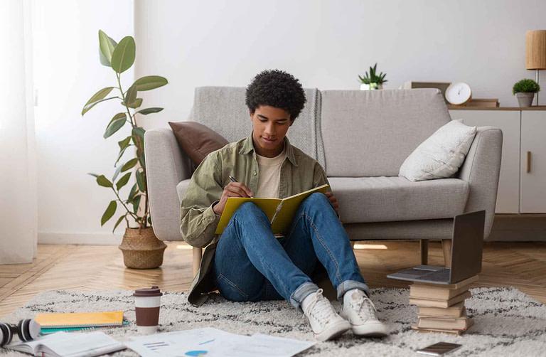 web-based-education-focused-black-teenager-writing-CTUZ5UH