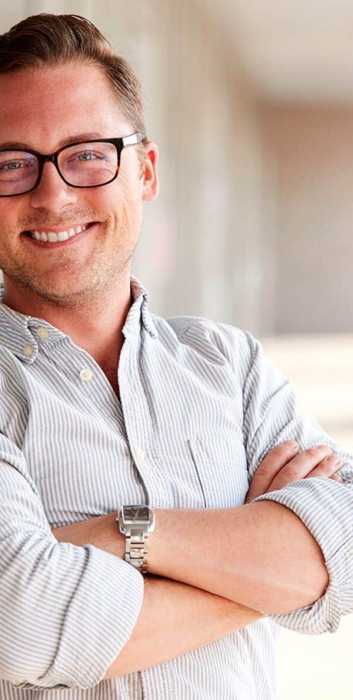 portrait-of-smiling-male-school-teacher-standing-i-7KLZDMS